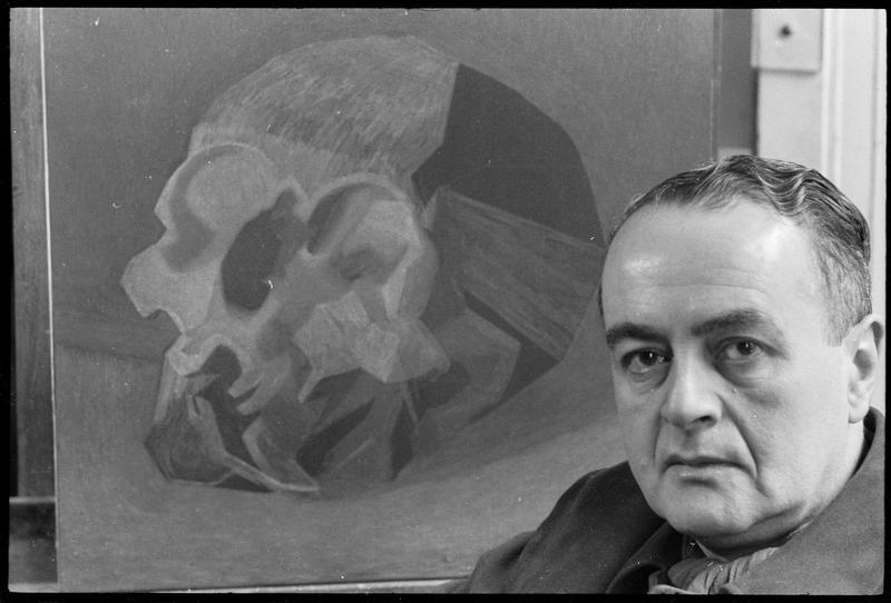 [Portrait de Luis Fernandez Lopez dans son atelier à côté d'une peinture représentant un crâne]