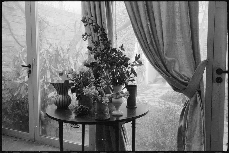 [Table ronde avec fleurs et vue sur le jardin intérieur]