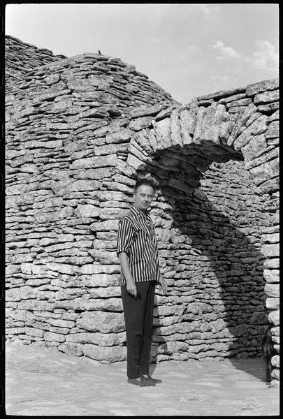 [Portrait de Victor Vasarely devant l'entrée de sa propriété surmontée d'une arche en pierre sèche]