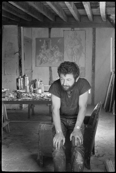 [Portrait de Dado assis dans son atelier devant une table de travail]