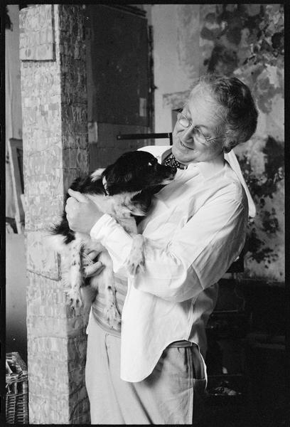 [Portrait de Joe Downing dans son atelier portant dans les bras son chien]