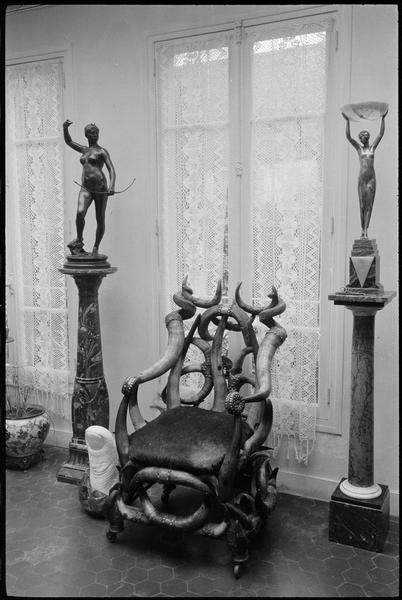 [Salon décoré de deux statues reposant sur des colonnes en marbre, d'un fauteuil en cornes et d'un 'Pouce' de César]