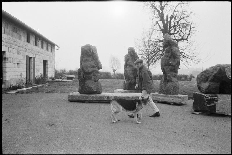 [Portrait d'Eugène Dodeigne avec son chien dans son jardin orné de ses sculptures]