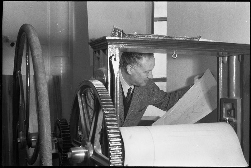 [Portrait de Marino Marini dans son atelier regardant une gravure derrière une presse à rouleau]