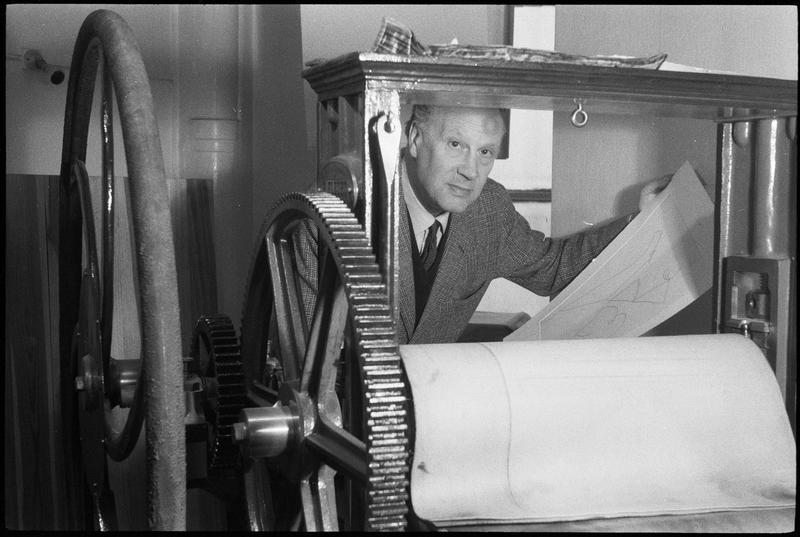 [Portrait de Marino Marini dans son atelier tenant une gravure derrière une presse à rouleau]