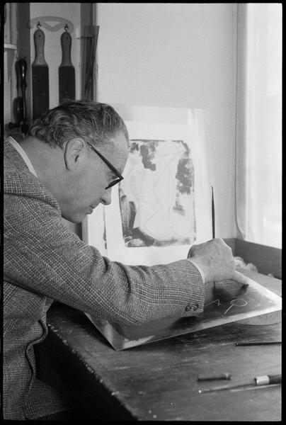 [Portrait de Marino Marini attablé dans son atelier gravant une plaque]