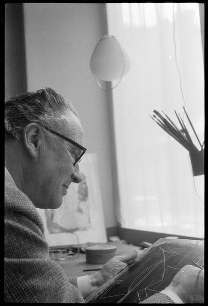 [Portrait de Marino Marini attablé dans son atelier tenant une plaque]