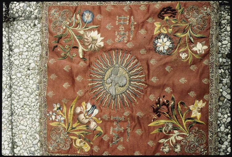 Voile de calice : satin rouge brodé de fleurs en fils de soie de différentes couleurs, motif central représentant la colombe de l'Esprit Saint, brodé de fils d'argents, bordure agrémentée d'une résille en fils d'argent