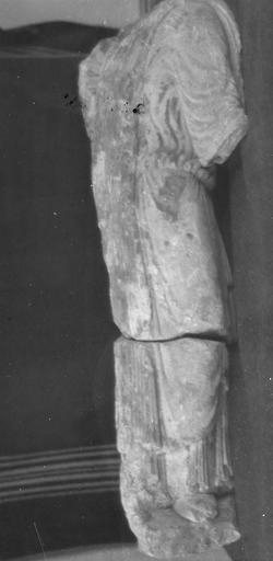 Statue : roi en prière, trouvée en 1952 (provient de l'ancienne abbaye de Saint-Père), vue de dos, le vêtement passe sur l'épaule gauche et retombe sur le dos, gros plissements à la taille