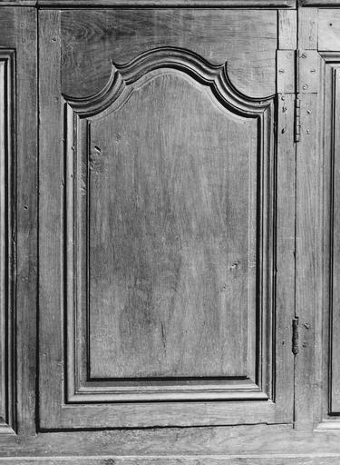Détail d'un des bancs de la nef, porte en bois