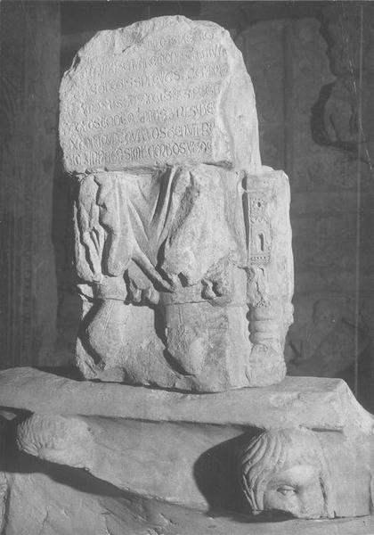 Statue : Personnage assis dans une cathèdre romane tenant sur les genous une épitaphe