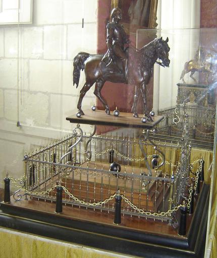 Statue, socle, piédestal : portrait équestre du comte de Chambord sur un socle en bois à volutes, sur un piédestal en bois encadré de grilles en laiton et fer, et de chaînes