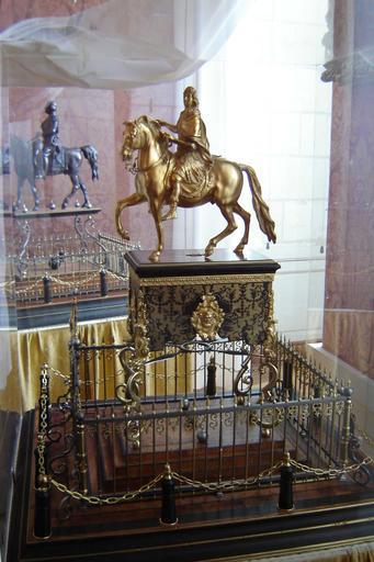 Statue, socle, piédestal : portrait équestre de Louis XIV sur socle en marqueterie d'écaille et de laiton, sur un piédestal en bois encadré de grilles en fer et laiton, et de chaînes