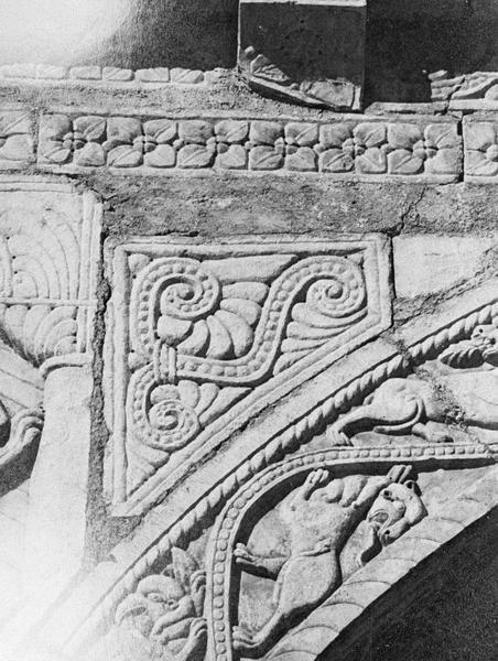 Maison abbatiale : portail sculpté, détail de l'écoinçon gauche orné d'une pierre triangulaire stylisée et claveau avec griffons (tympan transféré dans la galerie du cloître)