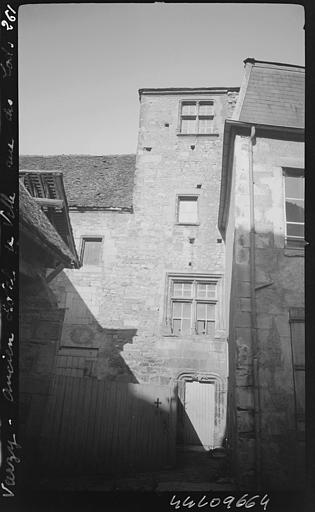 Angle de façades : porte d'entrée avec entourage en pierre sculptée, surmontée d'une fenêtre à meneaux