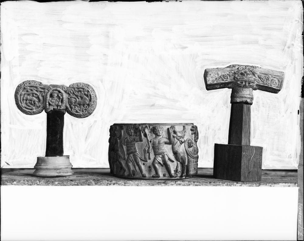 Deux taus encadrant une pyxide : tau à douille creusée d'une niche, tau avec rinceaux et tête de lion, pyxide cylindrique