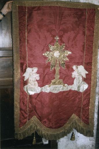 Bannière de procession de saint Hilaire, damas de soie rouge et applications, 18e siècle, vue de la face décorée d'un motif de deux anges en prière devant une gloire