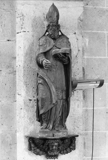 Statue sur console décorée d'une tête d'ange : saint Augustin tenant un livre, bois, 17e siècle