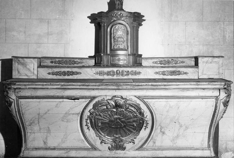 Autel, bois sculpté, 18e siècle avec au centre un médaillon contenat un motif de gloire, au dessus le tabernacle est orné d'un motif d'agneau pascal