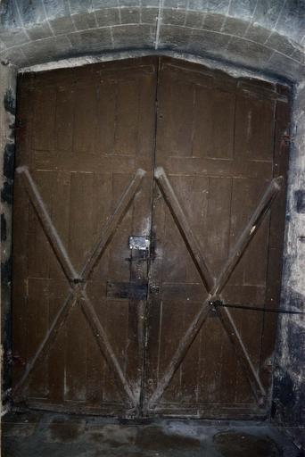 Vantaux d'une porte d'église, bois sculpté décoré de plis serviette, cloutage et ferronnerie d'origine, début 16e siècle, vue de l'avers