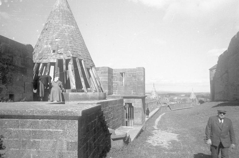 Tour de la Porte Rouge : toiture conique (en ruines) sur lices basses et tours de la Glacière et de Moureti en arrière-plan, vue animée