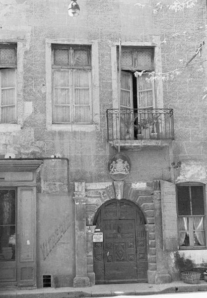 Façade sur rue avec portail d'entrée surmontée d'un blason