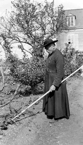 Curé travaillant dans son jardin