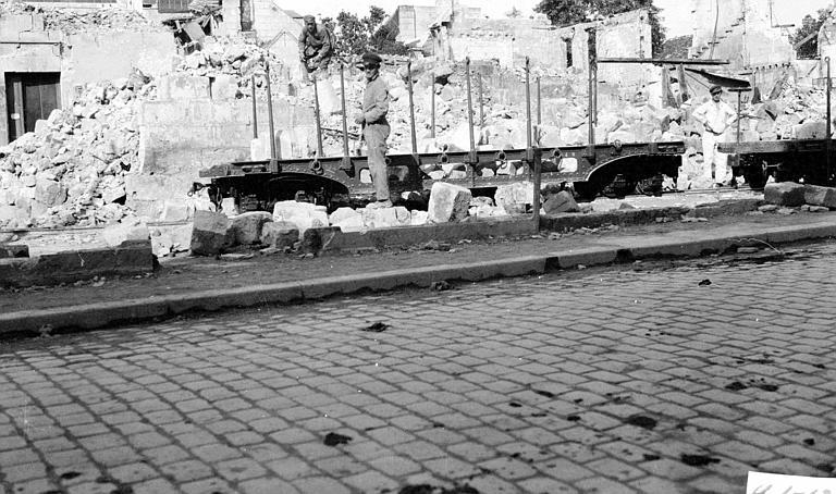 Travailleurs du comité réparant des maisons : pierres sur un wagon à ridelles