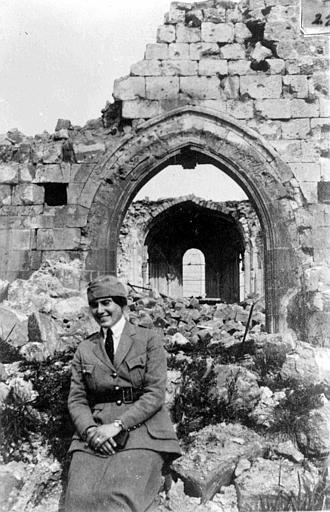 Mme Cordeley, membre du CARD, posant devant une façade ruinée de l'église