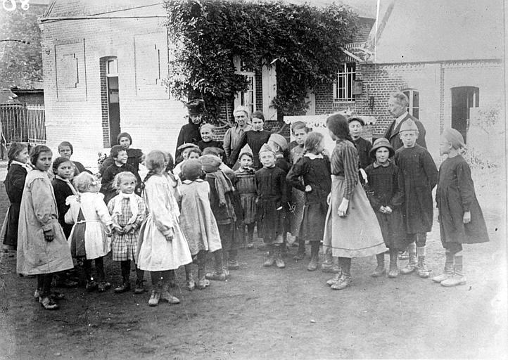 Mme Greggs visitant l'école à Aubigny : enfants dans la cour de récréation