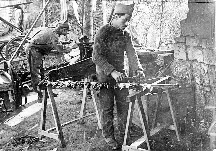 Ateliers du Comité Américain, réparation des machines agricoles démolies par les allemands : règlage des lames d'une faucheuse