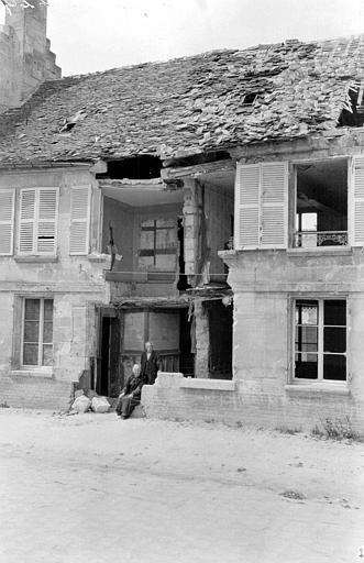 Maison de M. et Mme Dargent, rue du Château Blérancourt immédiatement après leur retour : les occupants assis devant leur façade évntrée