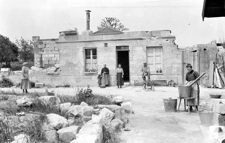 Réparation temporaire d'une maison : Mme Taylor à gauche, un groupe de trois femmes et un homme posant devant leur maison