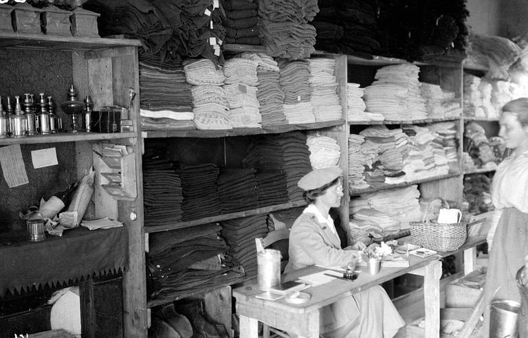 Intérieur du magasin du comité : Mme Braley Esther (travailleuse du CARD) devant une étagère pleine de linge