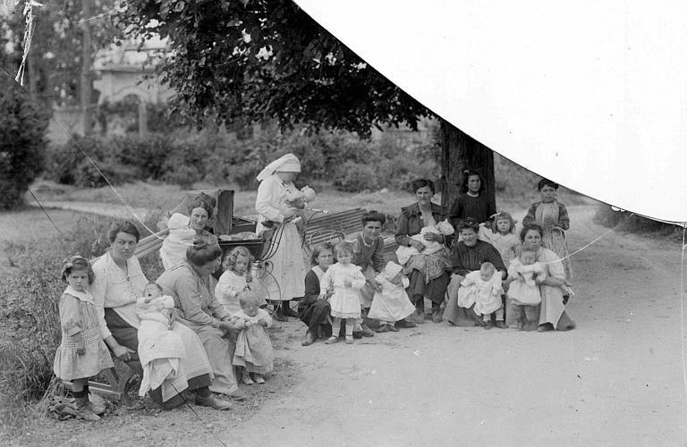 Le début du service de santé publique à Vic-sur-Aisne : Mme Mary Breckenridge en consultation, groupe de femmes et d'enfants posant à l'extérieur