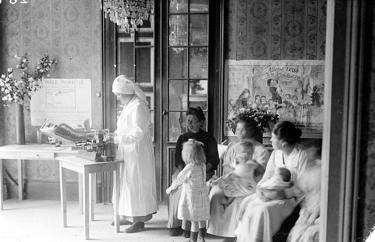Service de santé publique, consultation pédiatrique, intérieur : Mme Mary Breckenridge pesant un bébé, groupe de mères avec leurs enfants, affiches de propagande médicale aux murs