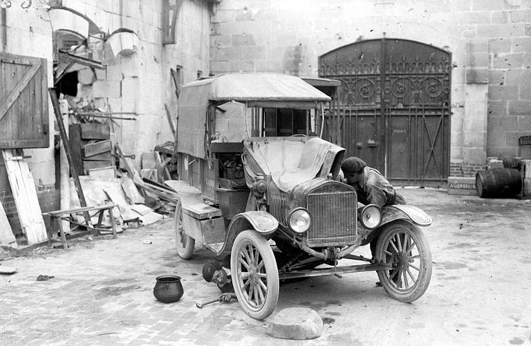 Service automobile de l'ACDF, cour : chauffeuse du comité réparant une voiture Ford