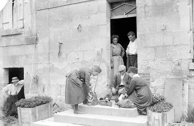 Perron d'une maison : docteur et infirmière soignant une blessure au membre inférieur d'un vieil homme, voisinage de Vic-sur-Aisne