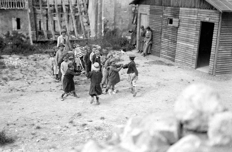Au milieu des ruines : la cour de récréation au printemps 1919, les enfants et Mlles Parsons et Garney
