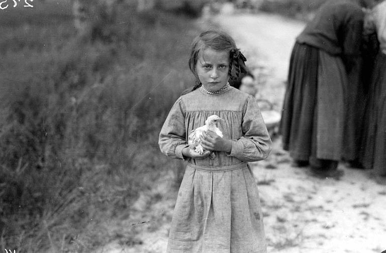 Petite fille en blouse d'écolière avec un poussin dans les bras