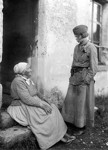 Mlle Moran, chauffeuse du docteur Tallant et travailleuse de l'ACDFet une vieille paysanne assise devant sa porte