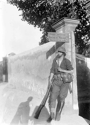 Foyer du soldat du Comité Américain : soldat américain en armes, en position de repos à l'entrée du foyer (pancarte avec les instructions d'accès au foyer)
