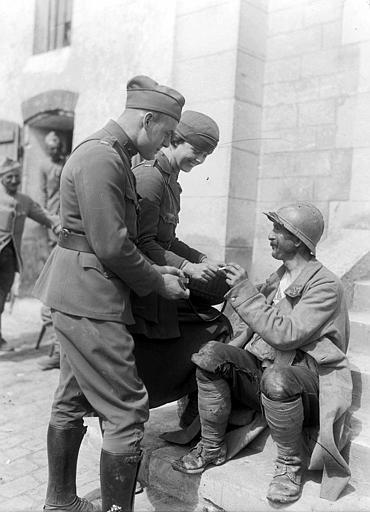 Pendant la retraite de 1918, service de cantine avec Mlle Jean Micheler de New York avec un militaire américain : distribution d'une cigarette à un soldat français du 51e régiment assis sur un escalier