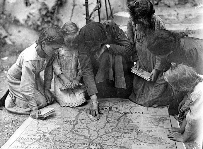 Ecole : cours sur une carte de France à des enfants, à même le sol