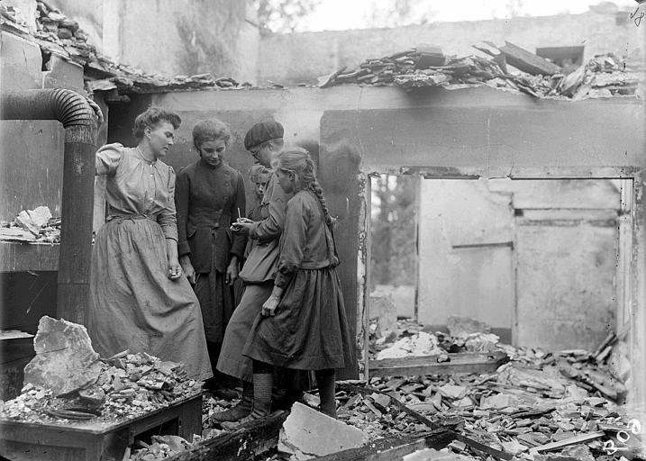 Les ruines après la retraite : restes de l'intérieur d'une maison, Barbara Allen, une travailleuse du CARD, prend des notes