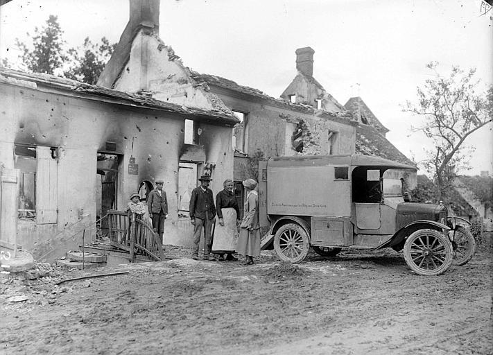 Réfugiés devant les ruines de leur maison avec Lucile Atcherson, membre du Comité Américain