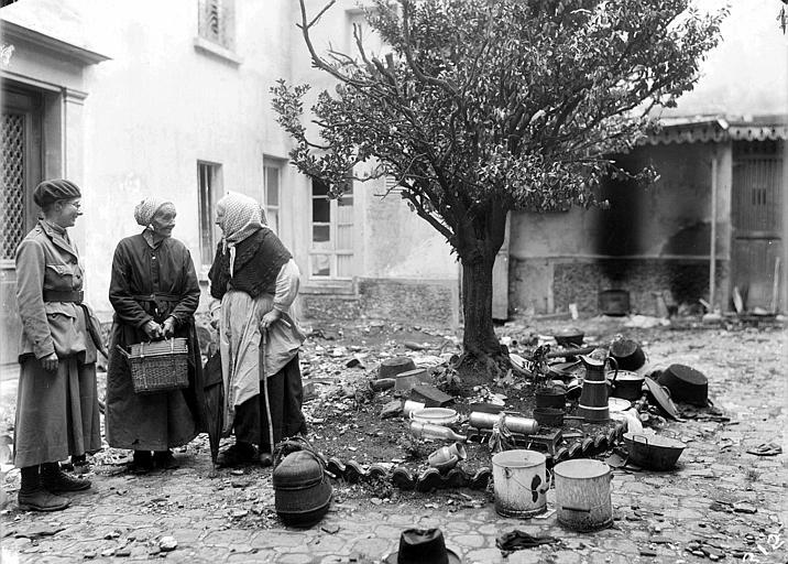 Barbara Allen, membre du CARD et des vieilles femmes dans une cour, ustensiles de cuisine à même le sol (acte de pillage)