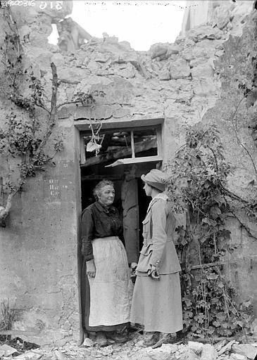 Lucile Atcherson, employée du CARD devant le reste d'une porte d'entrée parlant avec une réfugiée sur le seuil