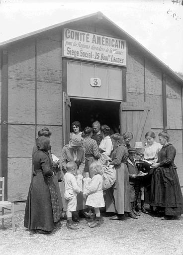 Entrepôt n°3 du CARD pendant la retraite de 1918 : Lucile Atcherson avec des réfugiés, distribution de jouets et de livres