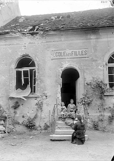 Ruines : école 'réouverte', groupe de fillettes assises sur l'escalier lisant